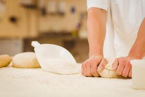 Baker kneading dough at a counter in a commercial kitchen