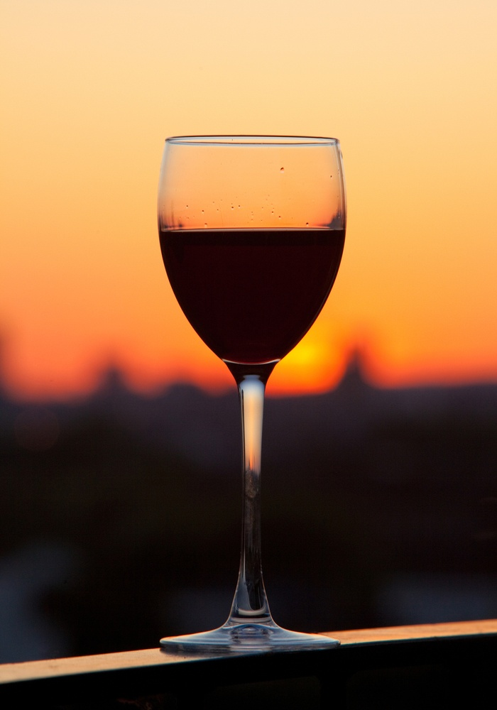 Glass of wine with a beautiful sunset as the background
